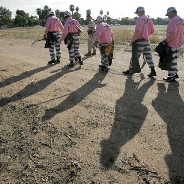 In this Dec. 11, 2007, file photo, members of the Maricopa County DUI chain gang are escorted to their assignment in Phoenix. As the nation on Thursday, June 17, 2021 officially made Juneteenth a federal holiday, honoring when the last enslaved Black people learned they were free, lawmakers are reviving calls to end a loophole in the Constitution that has allowed another form of slavery to thrive. (AP Photo/Matt York, File)